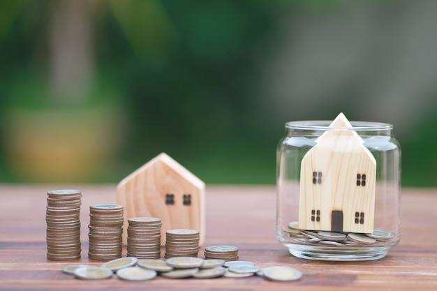Modello di casa con pila di monete di denaro sulla tavola di legno su sfondo sfocato.