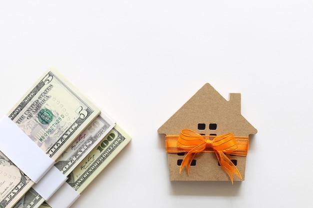 Casa modello con nastro arancione e banconota