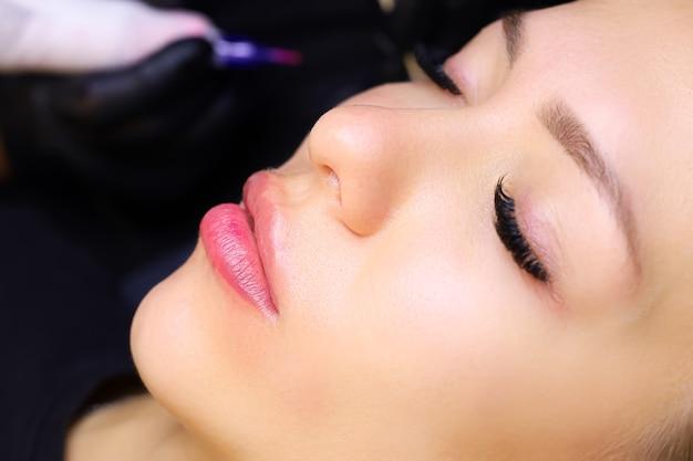 La modella è sdraiata con gli occhi chiusi già realizzati con la procedura di trucco permanente labbra