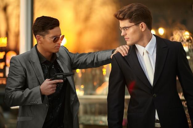 Modello uomo con occhiali da sole e con una pistola in mano che tiene in ostaggio un giovane uomo d'affari fiducioso.