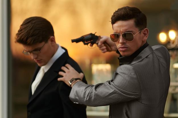 Modello uomo con occhiali da sole e tuta, con una pistola in mano che tiene in ostaggio un uomo d'affari.