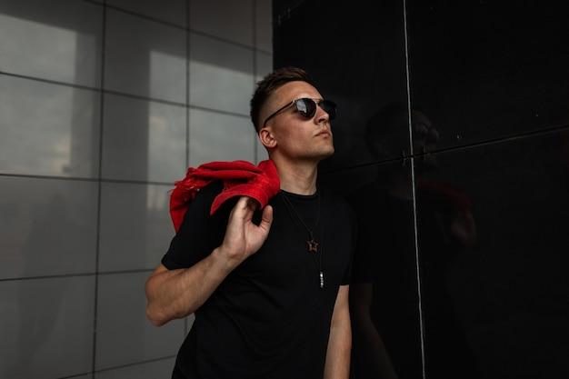 Il modello di un bel giovane in occhiali da sole alla moda con un gilet di jeans rosso alla moda in una maglietta nera si trova vicino a un muro nero in città.