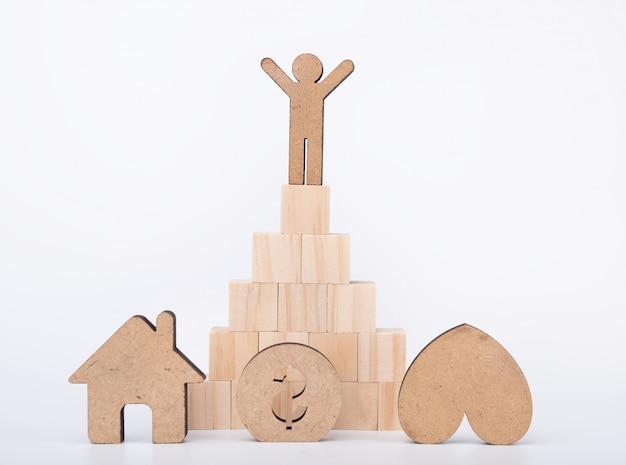 Le persone modello stanno sul gradino dei cubi con casa, soldi, cuore su bianco, concetto di vita di successo