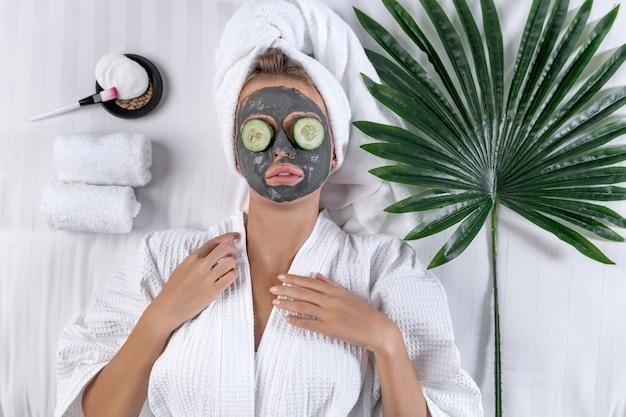 Una modella posa in un accappatoio bianco e un asciugamano sulla testa posa con una maschera di argilla sul viso e cetrioli sugli occhi sdraiata su un letto su cui giace una foglia di palma e asciugamani di spugna attorcigliati