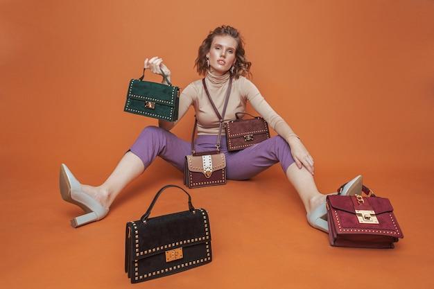 Modello in posa sul pavimento con cinque borsette.