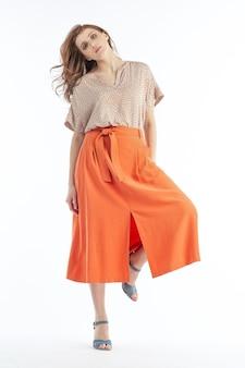 Modello in posa per la foto con la camicetta leggera e la gonna arancione
