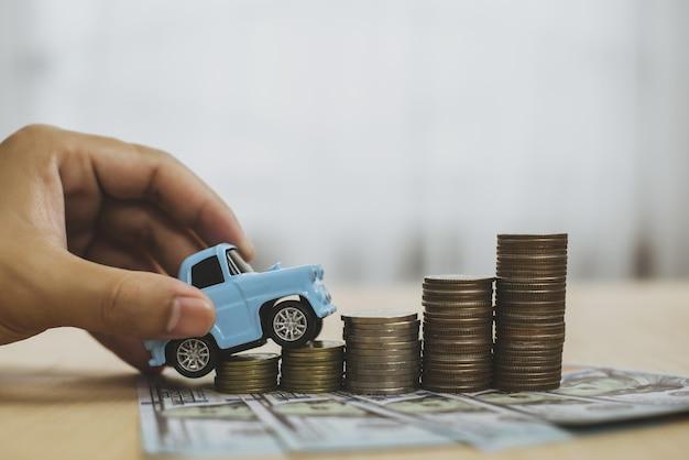 Modello di collare azzurro parcheggio giocattolo su pila di monete modello di auto su pila di monete saving finance loa