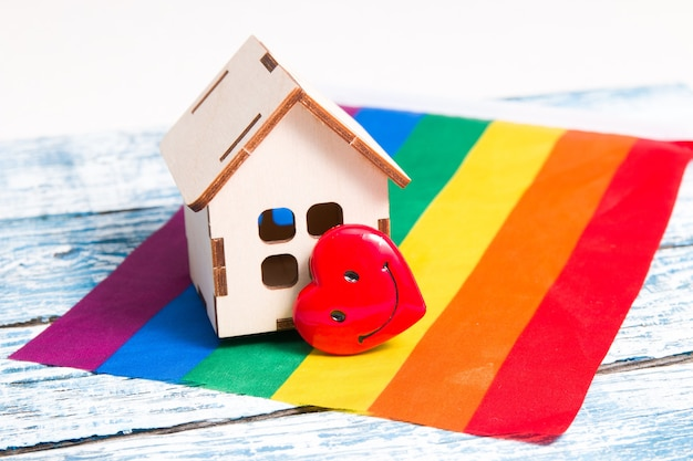 Un modello di una piccola casa in legno e un cuore sulla bandiera dei colori dell'arcobaleno