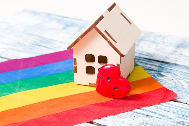 Un modello di una piccola casa di legno e un cuore stanno sulla bandiera dei colori dell'arcobaleno, una superficie di legno blu