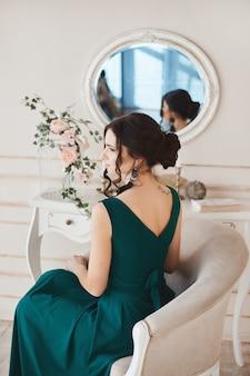 Modello in abito da sera elegante si siede vicino alla toletta