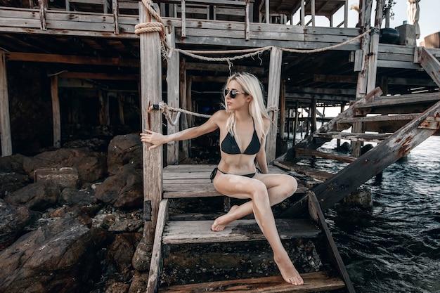 Modella che indossa un bikini nero e occhiali da sole e seduta su una scalinata di una baia di legno guardando di lato tra rocce e acqua.