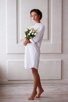 Modella in abito bianco con un mazzo di fiori. look estivo. presente