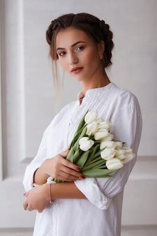 Modella in abito bianco con bouquet di tulipani. trucco estivo
