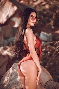 Modello con grandi seni in un costume da bagno rosso pone sulla spiaggia di sabbia nera.