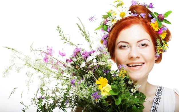 Modello con ampia acconciatura e fiori tra i capelli e con bouquet di fiori.