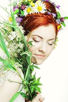 Modello con ampia acconciatura e fiori tra i capelli e con bouquet di fiori