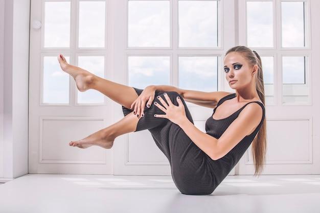 Modello donna in abito nero elastico con una bella silhouette sexy e trucco luminoso contro la finestra