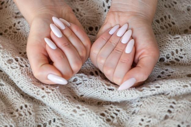 Modello donna che mostra la manicure gommalacca nudo rosa pallido chiaro su lo