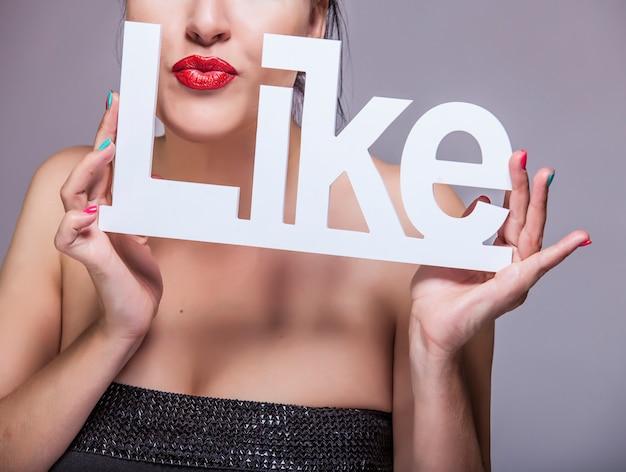 Modello donna con labbra rosse con lettere bianche come nelle mani