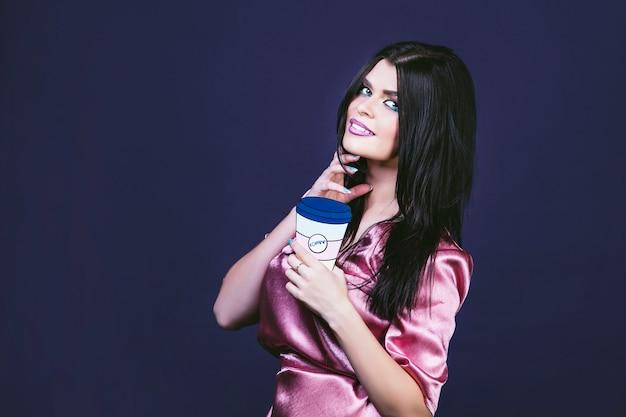 Modello donna giovane e bella in stile pop art su sfondo viola con l'immagine di una tazza di caffè