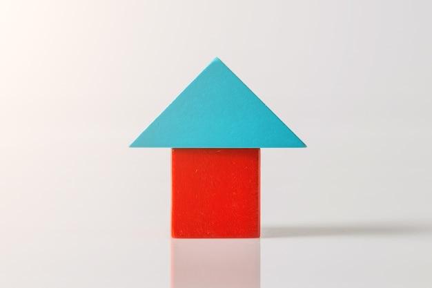 Modello della casa in legno (immobiliare) su uno spazio bianco