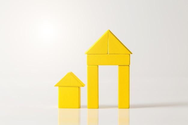 Modello della casa in legno (immobiliare) sul muro bianco