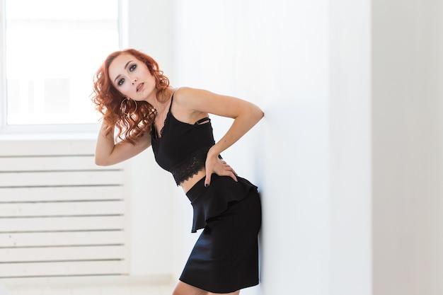 Modellazione, concetto di persone - attraente giovane donna in posa vicino al muro