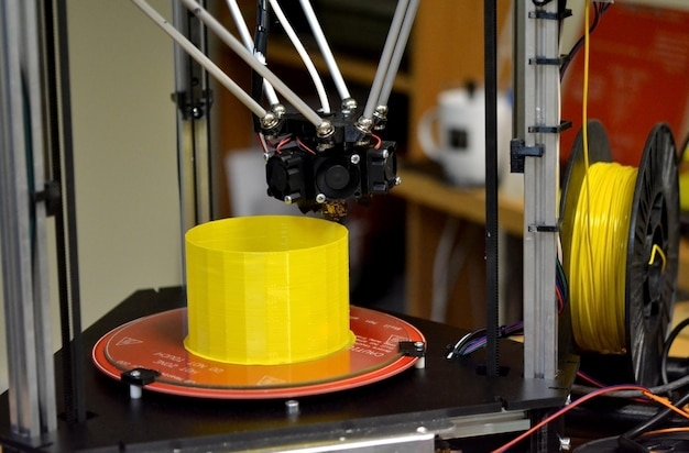 Primo piano moderno della figura di stampa della stampante 3d. la stampante 3d tridimensionale automatica esegue la modellazione di colori gialli in plastica in laboratorio. tecnologia additiva moderna e progressiva