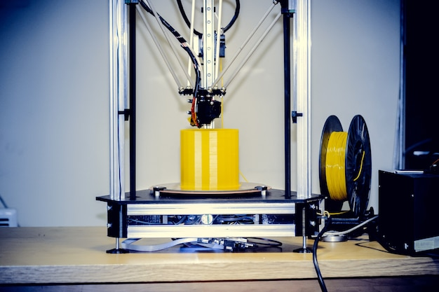 Primo piano moderno della figura di stampa della stampante 3d. copia spazio. la stampante 3d tridimensionale automatica esegue la modellazione di colori gialli in plastica in laboratorio. tecnologia additiva moderna e progressiva. filtro.