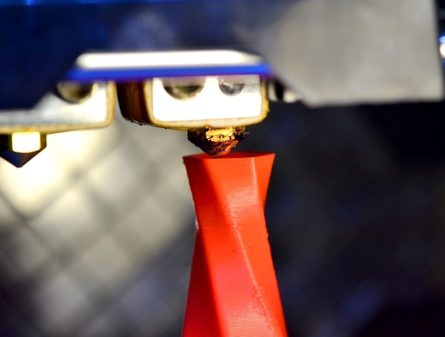 Macro moderna del primo piano della figura di stampa della stampante 3d. la stampante 3d tridimensionale automatica esegue la modellazione in plastica dei colori rosa e blu in laboratorio.
