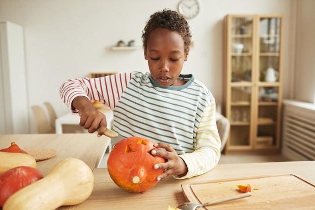 Ragazzo afroamericano moderno che indossa abbigliamento casual in piedi al tavolo a casa intaglia la faccia sulla zucca per la festa di halloween