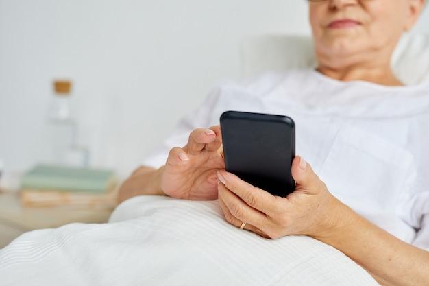 Donna invecchiata moderna che indossa vestiti bianchi che si distendono sul letto in messaggi di sms del reparto di ospedale utilizzando il suo smartphone