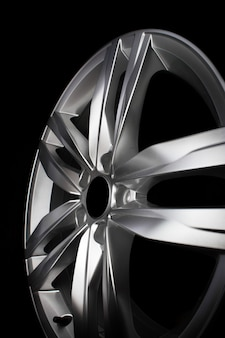 Cerchio auto moderno in lega di alluminio isolato su sfondo nero.