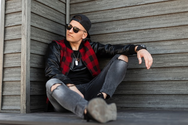 Uomo moderno bello giovane hipster americano in vestiti alla moda in un berretto da baseball nero alla moda in occhiali da sole alla moda si siede e gode di una calda giornata estiva