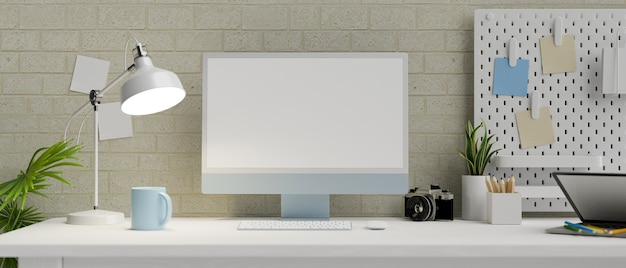 Moderno spazio di lavoro in appartamento con computer desktop a schermo vuoto e cose in un moderno muro di mattoni