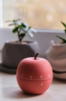 Timer moderno a forma di mela accanto alle finestre con calda illuminazione all'alba