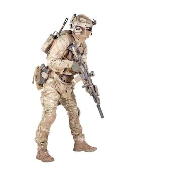 Fuciliere di fanteria dell'esercito moderno in uniforme mimetica, auricolare radio sul casco, munizioni sul vettore di carico, furtivamente, accovacciato, mirando e sparando con tiro in studio fucile di servizio isolato su sfondo bianco