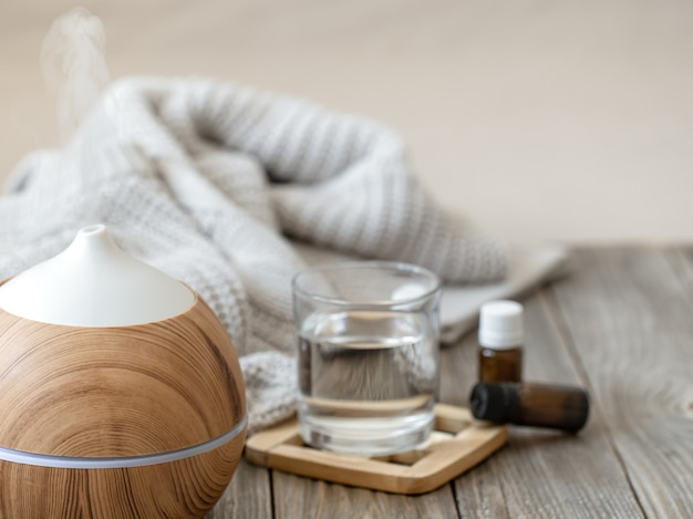 Diffusore moderno di oli aromatici su superficie in legno con elemento in maglia, acqua e oli in barattoli.
