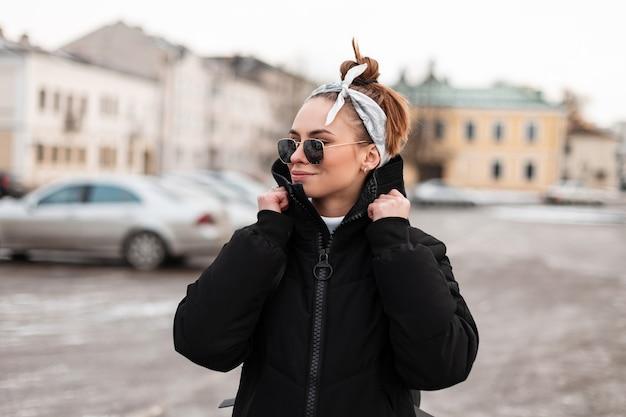 Donna moderna attraente giovane hipster in abiti invernali alla moda con un hairdress con una bandana in occhiali da sole nella città di edifici d'epoca. elegante ragazza americana viaggia.