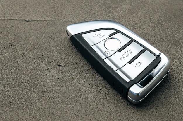 Chiave dell'automobile dell'automobile moderna su priorità bassa concreta nera