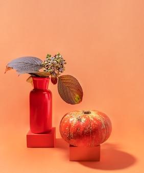 Autunno moderno natura morta con zucca e foglie con bacche in vaso rosso su podi alla moda su sfondo arancione sottile con spazio di copia