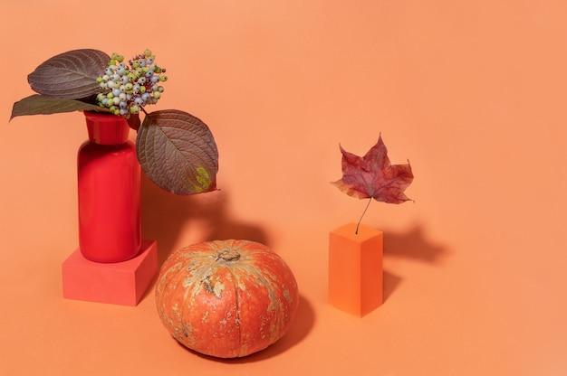 Autunno moderno natura morta con zucca, foglie con bacche su podi alla moda su sfondo arancione sottile con spazio di copia