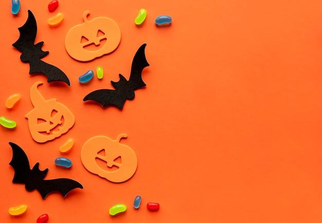Sfondo moderno con pipistrelli zucche caramelle su sfondo arancione