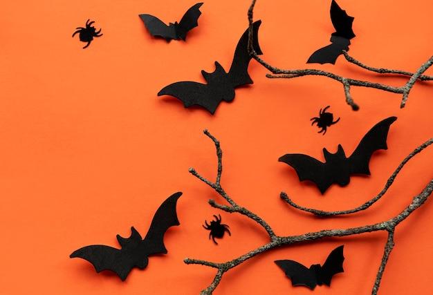 Il fondo moderno con le zucche dei pipistrelli lascia i ragni su un fondo arancione