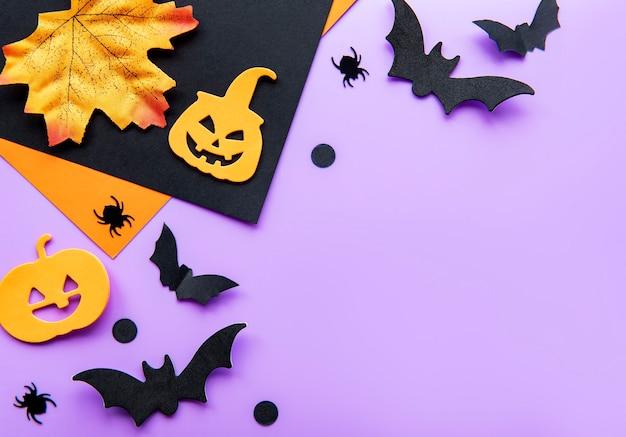 Il fondo moderno con le zucche dei pipistrelli lascia i ragni su un fondo viola
