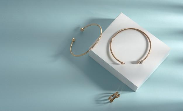 Braccialetti moderni e anello a forma di catena su sfondo bianco e blu con spazio di copia