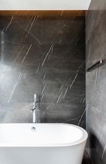 Interno del bagno moderno con vasca da bagno e parete in marmo naturale marrone / interior design / spazio della copia