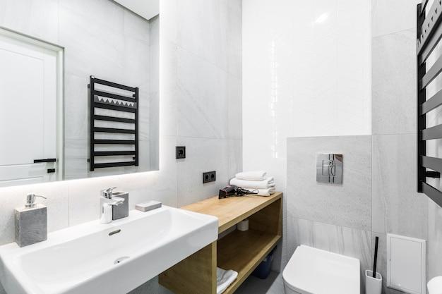 Bagno moderno con doccia in un piccolo appartamento con piastrelle in marmo bianco
