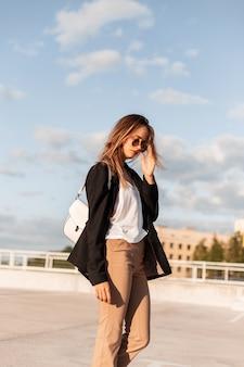 Bella donna moderna in abiti da lavoro alla moda con borsa cammina nel parcheggio e raddrizza gli occhiali. ragazza abbastanza attraente in elegante abito casual in giornata di sole su sfondo azzurro del cielo.