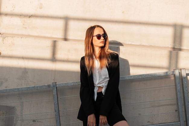 La bella giovane donna moderna in occhiali da sole d'annata in camicia bianca classica in rivestimento alla moda nera riposa vicino all'edificio in città al tramonto luminoso. attraente ragazza fresca in abbigliamento casual giovanile all'aperto.